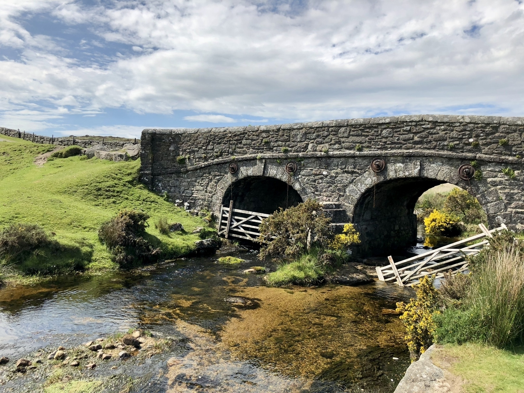 A stone bridge over a creek with mossy grass on the banks